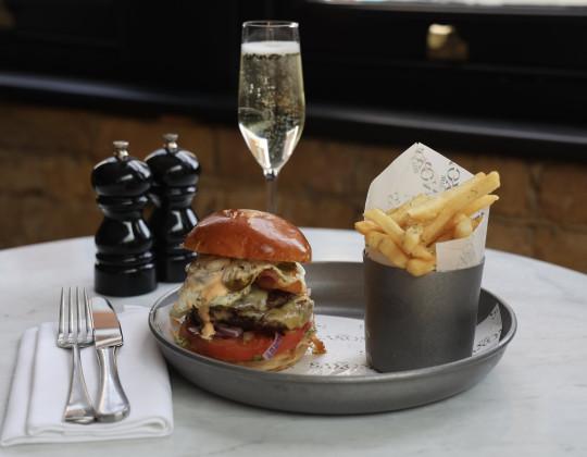 Hamburguesa, patatas fritas y una copa de champán en The Saxon