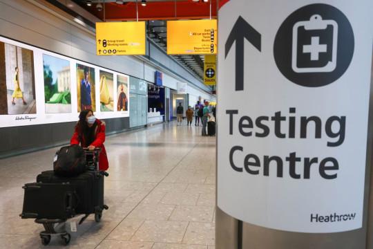 Un viajero pasa una señal para un centro de pruebas Covid-19 en el aeropuerto de Heathrow en Londres