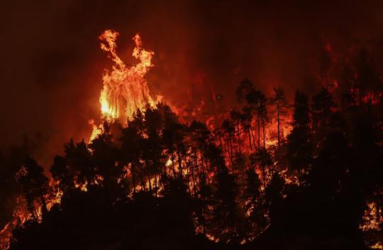 Las llamas se acercan a la aldea de Gouves en la isla de Evia, a unos 185 kilómetros (115 millas) al norte de Atenas, Grecia, el domingo 8 de agosto de 2021.