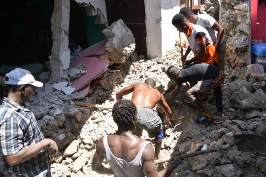 epa09414524 Un grupo de personas limpian los escombros provocados por un terremoto, en Puerto Príncipe, Haití, el 14 de agosto de 2021. Un terremoto de magnitud 7,2 dejó al menos 304 muertos, más de 1.800 heridos y causó considerables daños materiales, agravando el ya difícil situación del empobrecido país caribeño. EPA / Duples Plymouth