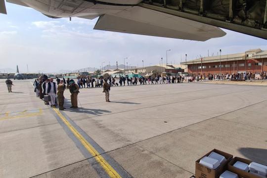 Los afganos hacen fila para ser evacuados en un avión C130J de la Fuerza Aérea Italiana desde el aeropuerto de Kabul, el domingo 22 de agosto de 2021. El sábado, Italia sacó a 211 afganos de Kabul, elevando a unos 2.100 el número de trabajadores afganos en las misiones italianas y sus familias. que han sido evacuados de manera segura de Afganistán, dijo el Ministerio de Defensa en un comunicado. (Ministerio de Defensa italiano vía AP)